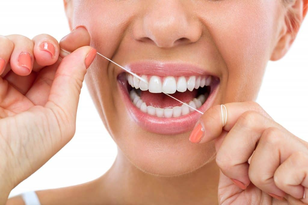 lady-brushing-and-flossing-her-gums