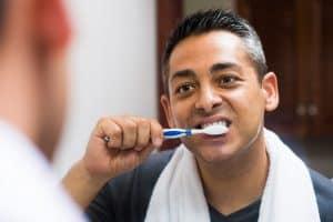 man brushing his teeth with fluoride