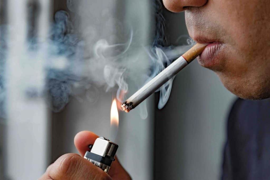 A person smoking a cigarette damaging teeth